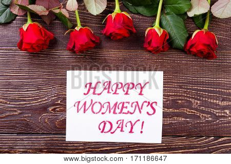 Women's Day card and roses. Greeting paper, roses, wooden background. Present flowers to dear lady. Send warm greetings.