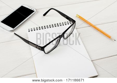 Black-rimmed Glasses With Open Notepad, Pencil And Smartphone On A White Wooden Table