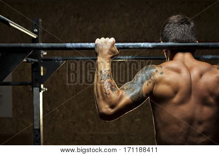 Muscular man with naked torso doing pull up exercise on horizontal bar in gym