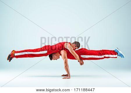 The two gymnastic acrobatic caucasian men posing in balance posture on gray studio background