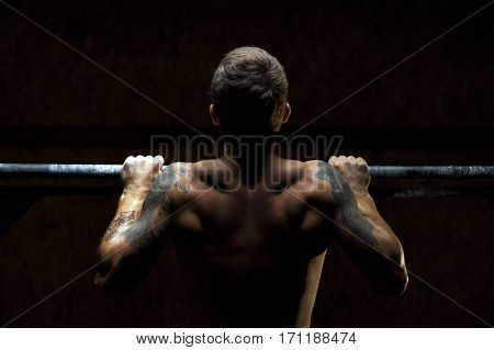 Strong muscular man doing pull up exercise on horizontal bar. Fitness, gymnastics workout in gym.