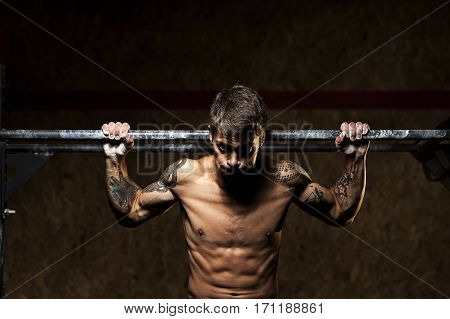 Muscular man with naked torso doing pull ups on horizontal bar. Gymnastics, fitness workout in gym.
