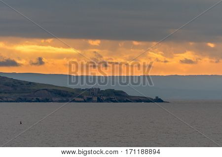 Fort on Brean Down, in front of sunset. An historic fort last used in World War II stands on rocks on the shore of the Bristol Channel in Somerset UK