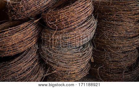 Background of the rusty hanks of an old barbed wire lying in military warehouses waiting for