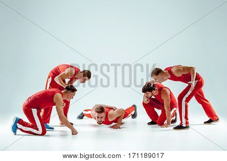 The group of gymnastic acrobatic caucasian men at training on gray studio background. Concept of sport injury and pain