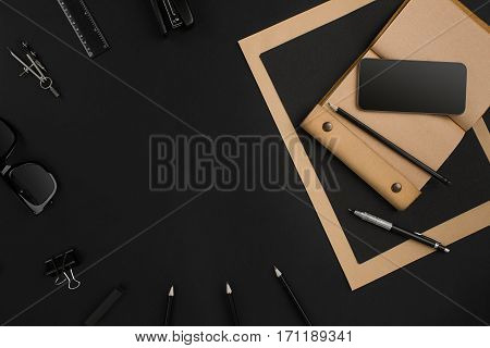 Office desktop with various black objects on black background. Top view. Still life