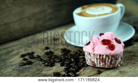 Cappuccino coffee and sweet cake. A cup of latte, cappuccino or espresso coffee with milk put on a wood table with dark roasting coffee beans. Drawing the foam milk on top.