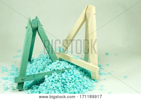 Blue and white wooden mini easels which are bombarded by small blue stones on a light background.