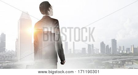 Businessman against modern city background . Mixed media