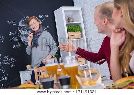 Young woman at blackboard wall with menu