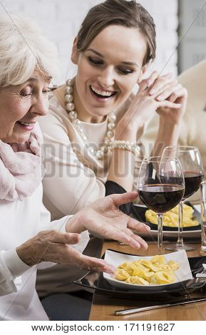 Young And Elderly Women Sitting At The Table