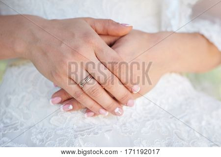 bride hand with a wedding ring on the background of dress.