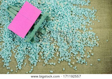 Blue Easel With Pink Paper For Inscriptions On The Crumbled Blue Gravel.