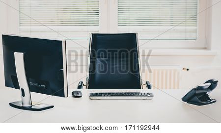 Modern empty office space desk with computer phone and chair. Concept of corporate job vacancy promotion financial world and business in general.