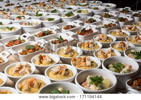 Buffet with appetizers, Russian salad, hummus with chicken, feta cheese with vegetables top view small portions