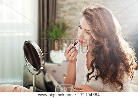 portrait of young woman looking in the mirror and rouge her lips with red lipstick