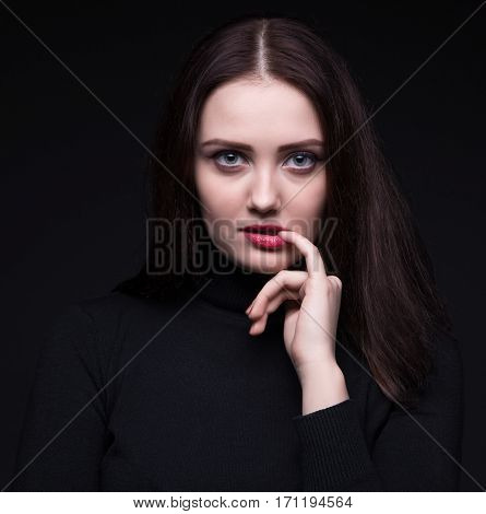 Portrait of woman with pinky finger on black background