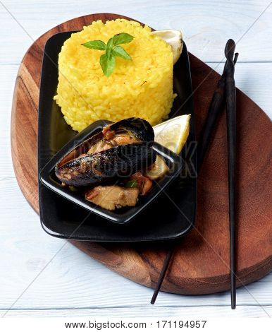 Arrangement of Delicious Seafood Curry with Mussels White Fish and Vegetables and Stack of Saffron Rice with Chopsticks on Serving Board closeup on Wooden background