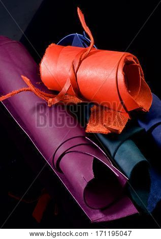 Stack of Colorful Leather in Rolls closeup on Black background