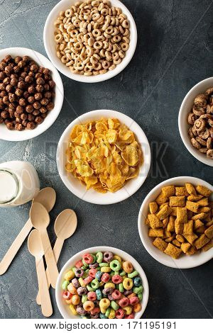 Variety of cold cereals in white bowls, quick breakfast for kids overhead shot