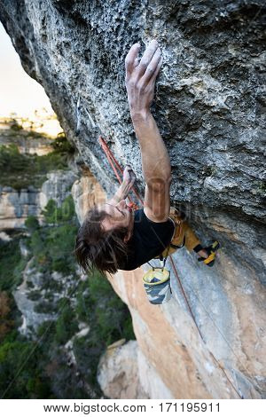 Outdoor sport. Rock climber ascending a challenging cliff. Extreme sport climbing.