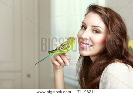 half length portrait of beautiful young woman with parrot on her hand