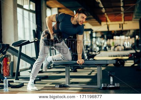 Young handsome man doing one-arm dumbbell back exercise on bench modern gym
