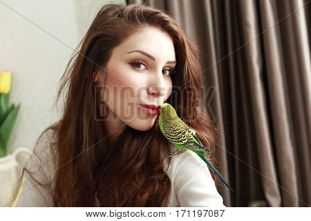 half length portrait of young woman with cute parrot on her shoulder giving her a kiss