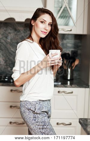 half length portrait of young woman standing on the kitchen with warm cup of coffee