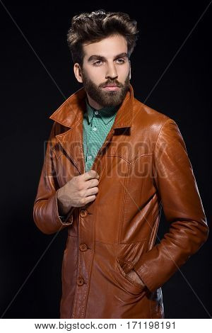 Young man with beard in a brown leather jacket posing on a dark background
