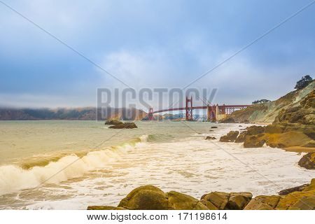 Spectacular bottom view of Golden Gate Bridge from Baker Beach, considered by many the most beautiful beach of San Francisco, California. Fog in summertime. Holidays, travel and leisure concept.