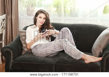 portrait of young woman relaxing on the sofa and listening to the music
