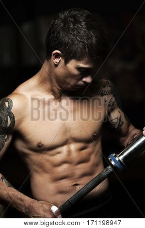 Young sporty man with naked torso holding barbell. fitness, weightlifting workout