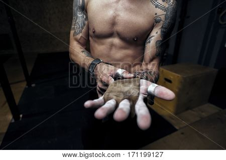 Cropped shot male athlete wearing gymnastics grips for doing pull up workout.