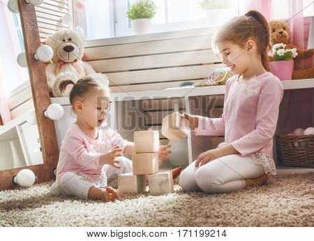 Two cute little children are playing with blocks. Happy girls at home. Funny lovely sisters are having fun in kids room.