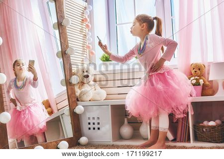 Cute little child is playing with phone. Happy girl takes photo selfie at home. Funny lovely princess is having fun in kids room.