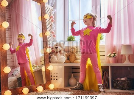 Little child plays superhero in the kids room. Girl power concept.