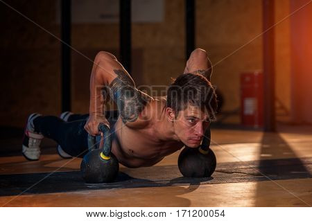 Sporty man with naked torso doing push up exercise with kettle bell. Fitness, sports concept.