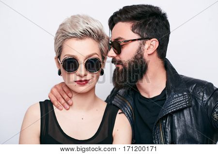 Pretty couple wearing fashion clothes whispering in others ear on white background. Close-up of Bearded man and blond model in sunglasses seducing