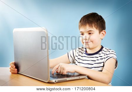 seven years old child sitting with a laptop at table and typing