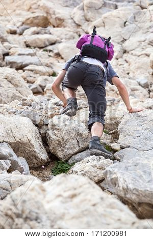 Climber with backpack crawling on rock of large stones, man climbs on top of mountain