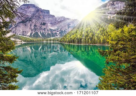 Beautiful lake in South Tyrol, Italy. The concept of walking and eco-tourism.  Sunshine on autumn day. Water reflects the surrounding mountains and forest