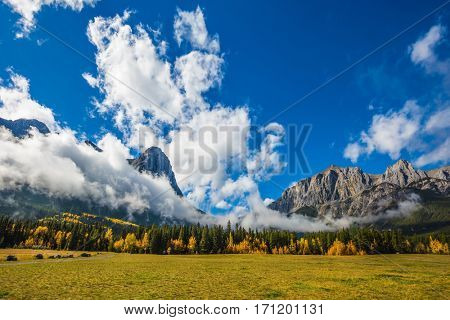 Concept of hiking. Auroral sunny day in Canmore. The famous Three Sisters mountains in the Canadian Rockies  of Canada
