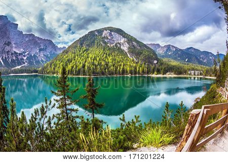 The pedestrian footpath around the lake is fenced with a wooden handrail. Magnificent Alpine lake Lago di Braies. Concept of ecological and pedestrian tourism