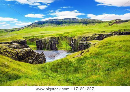 The concept of active northern tourism. The striking canyon in Iceland. Bizarre shape of cliffs surround the stream with glacial water. Green Tundra in July