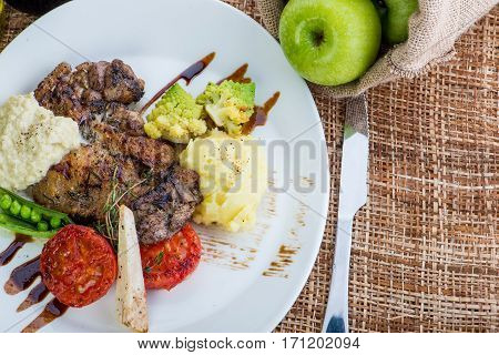 Steaks In Sage And Apple Sauce Served With Vegetables.roasted Beef Slices With Berry, Apple And Pear