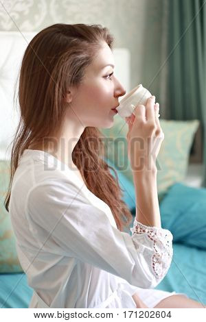 beautiful woman enjoying fresh coffee in the morning sitting on her bed