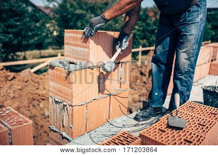 industrial construction worker professional bricklayer worker placing bricks on cement while building exterior walls industry details