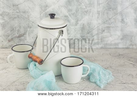 Two white cups and white enameled cans on light background