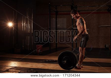 Male muscular athlete preparing to lift barbell in gym. Weightlifting, power lifting equipment. Sports, fitness - healthy lifestyle concept.